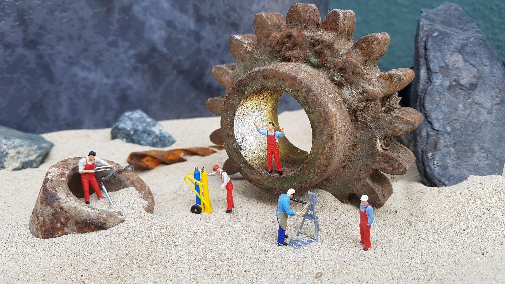 Statuette di plastica di operai, posizionati in uno scenario con sabbia e sassi.