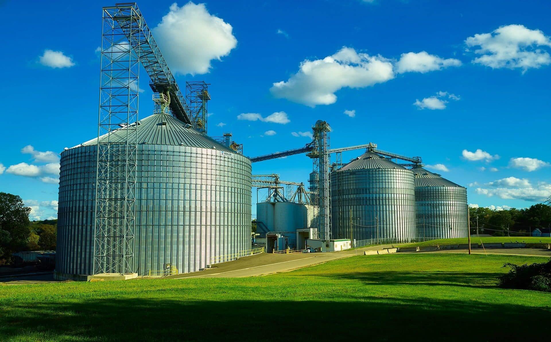 Tre cisterne industriali in mezzo a un prato e in una giornata di cielo sereno.