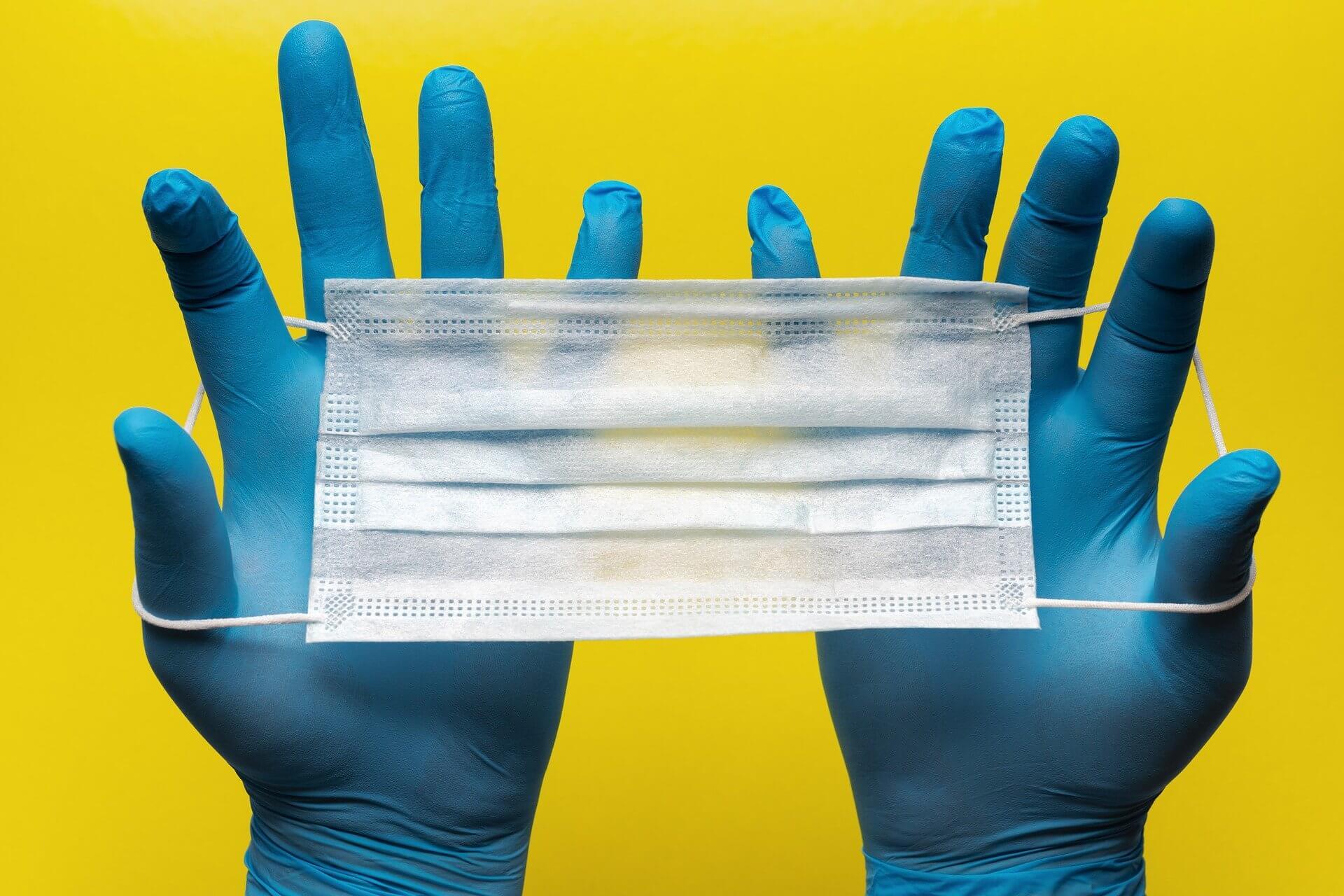 due mani con guanti blu che allargano una mascherina chirurgica bianca ed azzurra