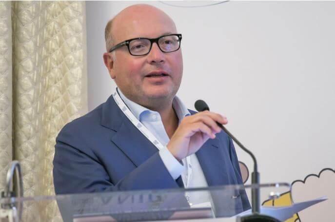 Lorenzo Mattioli che parla ad un convegno. Indossa una camicia chiara, una giacca azzurra e porta gli occhiali una camicia