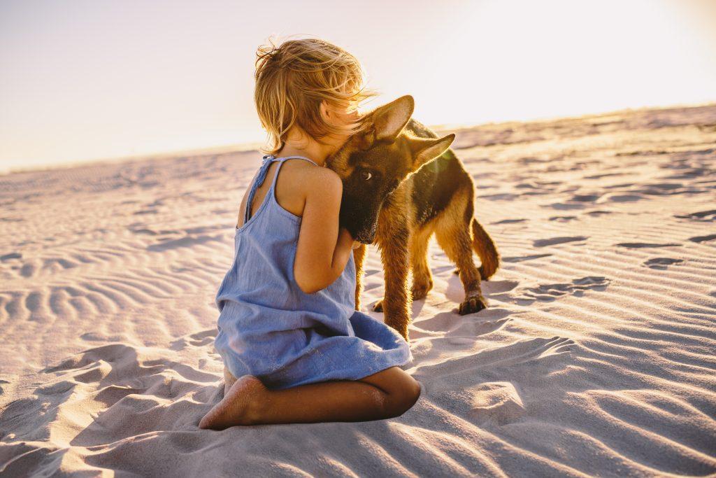 Bimbo e cane sulla sabbia