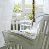 In una delle camere da letto, accanto alla sedia in legno decapato, un oggetto di arte topiaria realizzato con l'edera intrecciata.