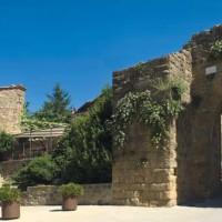 L'ingresso a Monticchiello, località che conserva ancora i tratti austeri delle fortezze medievali, contrasta con il carattere rinascimentale di Pienza.