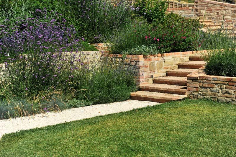 Il giardino è affollato di bordure miste di graminacee e piccoli arbusti