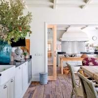 La cucina con mobili in stile Shaker è provvista di una scenografica cappa e di un pannello in acciaio