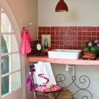 Piastrelle rosse, finestra ad arco e oggetti in ferro battuto caratterizzano uno dei bagni della casa.