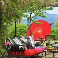 Una delle zone conversazione esterne, con arredi colorati, come l'ombrellone e le sedute in legno