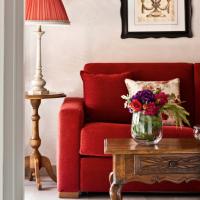 Un divano rosso, un vecchio tavolino in noce e un lume arredano questo angolo di relais