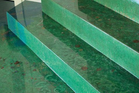 Scala rivestita con resina Dega Art decorata verde con polveri metalliche con finitura a spessore Poliepo, un rivestimento speciale per laccare pavimenti e superfici con l'effetto di una colata vetrificata. Le alzate sono sempre in Dega Art in finitura satinata.