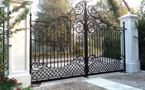 Cancello a due ante in ferro battuto che combina in modo armonico linee geometriche con elementi a morbide volute curvilinee.