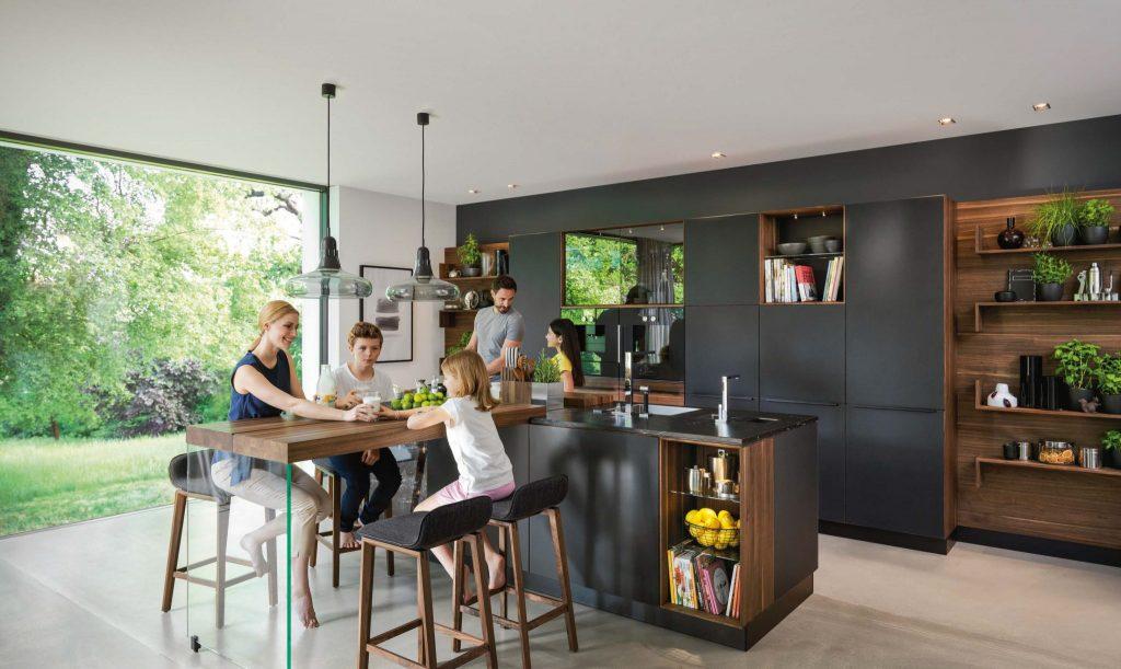 Team7 propone una cucina con un'isola attorno a cui si riunisce la famiglia